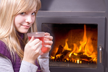 girl drinking tea near the fireplace....