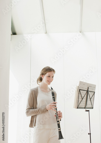 Smiling woman holding clarinet and looking at sheet music