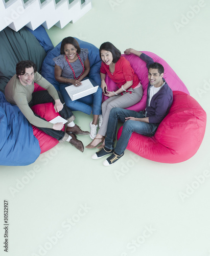 Smiling business people sitting in bean bag chairs