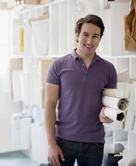 Smiling architect holding blueprints in office