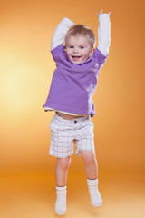 happy jumping cute boy in violet t-shirt