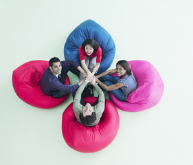 Smiling business people sitting in bean bag chairs with stacked hands