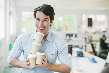 Smiling businessman balancing coffee cups