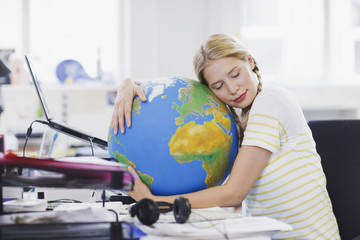 Businesswoman with eyes closed hugging globe at desk in office