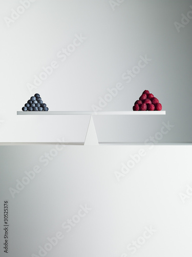 Blueberries and strawberries balanced on opposite ends of seesaw