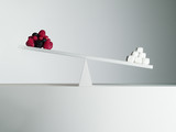 Sugar cubes tipping seesaw with berries on opposite end