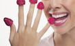 Close up of woman biting raspberries on fingertips