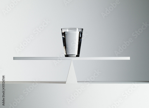 Glass of water balancing on middle of seesaw