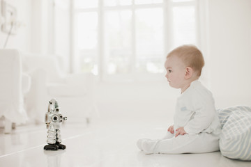 Baby on floor looking at toy robot