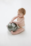 Babies playing with globe on floor