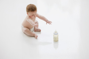 Baby on floor reaching for bottle of milk