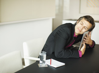 Smiling businessman hugging laptop in conference room