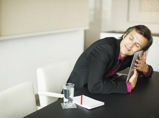 Smiling businessman hugging laptop in conference room