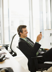 Smiling businessman text messaging with cell phone in office