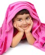 cute baby girl peeking out from pink blanket