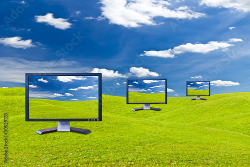 Lcd monitor on green grass meadow