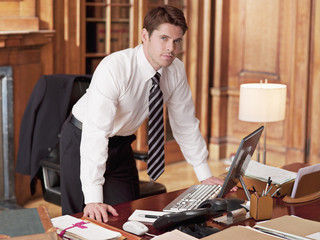 Serious lawyer working at laptop in office