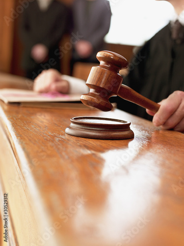 Close up of judge raising gavel in courtroom