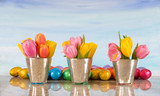 tulips in vases with foil eggs for easter