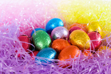 colorful foil wrapped eggs in nest for easter