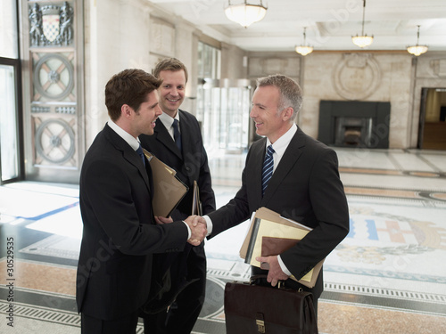 Smiling lawyers with files shaking hands in lobby