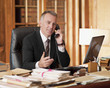 Lawyer talking on telephone and gesturing in office
