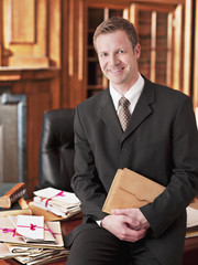 Smiling lawyer leaning on desk in office