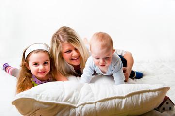 Mutter mit zwei Kindern auf dem Bett spielen