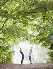 Women stretching before exercise near lake