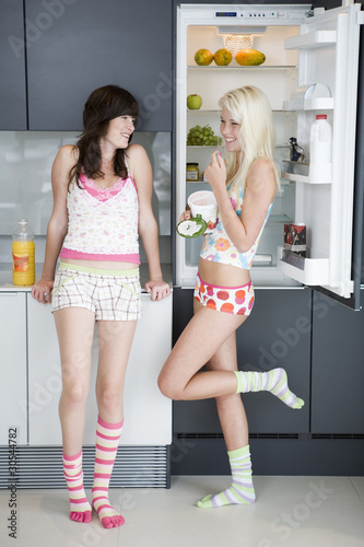 Friends eating from refrigerator together