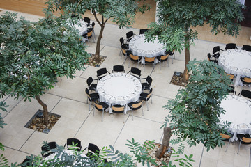 Empty chairs around circular tables in atrium