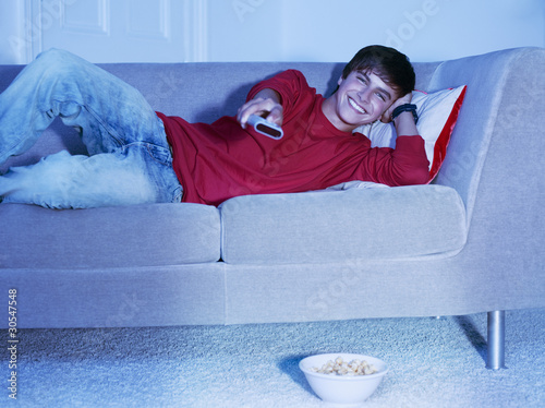 Smiling teenage boy laying on sofa with remote control