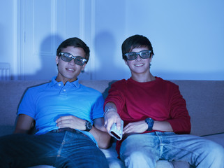 Teenage boys watching television with 3-D glasses