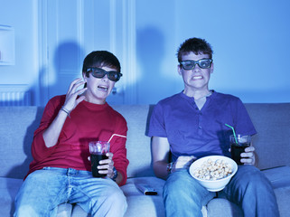 Teenage boys with snacks watching television with 3-D glasses