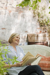 Smiling woman reading book on patio