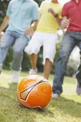 Teenage boys playing soccer together