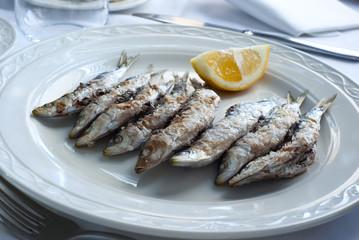 Gegrillte Sardinen auf Teller mit Zitrone