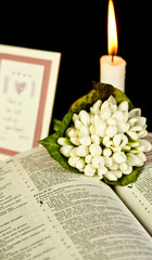 Open Bible with burning candle and white flowers