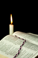 Open Bible with burning candle