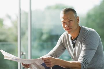 Serious man holding newspaper