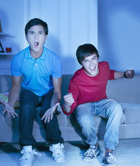 Shouting teenage boys watching television