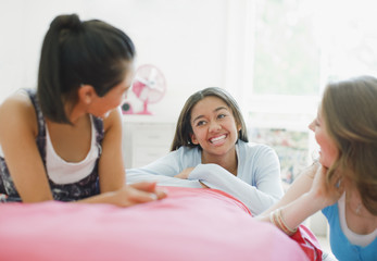 Smiling teenage girls talking in bedroom