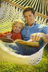 Father and son reading book in hammock