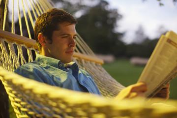 Man laying in hammock reading newspaper