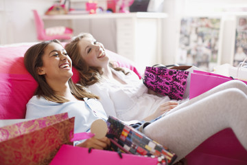 Teenage girls sitting on floor with shopping bags