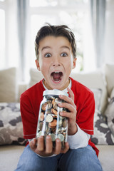 Surprised boy holding jar full of coins