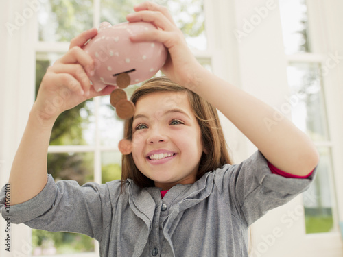 Excited girl emptying coins from piggy bank
