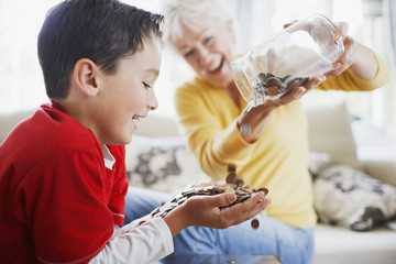 Grandmother emptying jar of coins into grandson?s hands