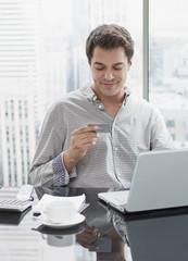 Businessman using credit card to shop on internet