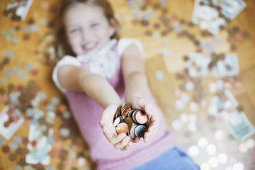 Girl laying on floor holding handful of coins